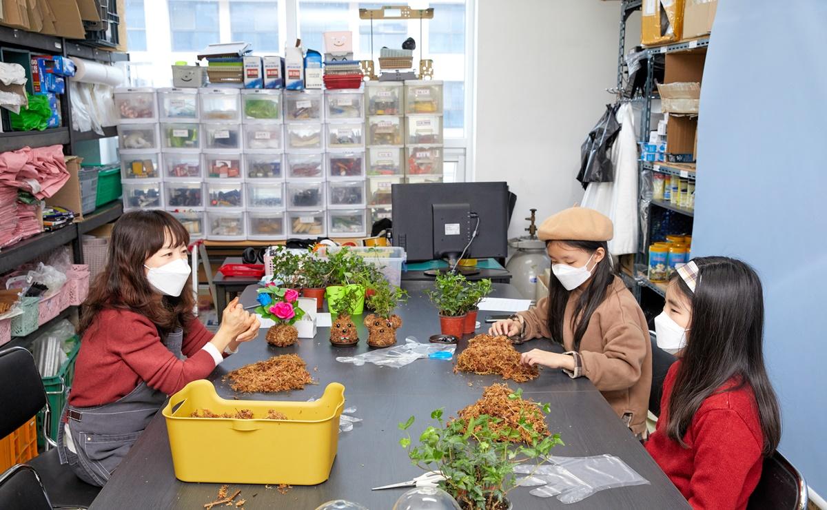 열린체험터 서은아 선생님(맨 왼쪽)이 소중 학생기자단에게 수태 토피어리 만드는 법을 설명했다.